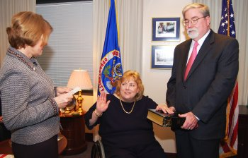 Commissioner Christine M. Griffin is sworn in by Chair Cari M. Dominguez as her husband looks on