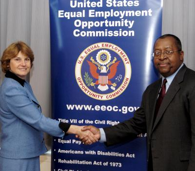EEOC Chair Dominguez and Joe Laymon, Ford's Corporate Vice President for Human Resources, shake hands after signing the NUAM