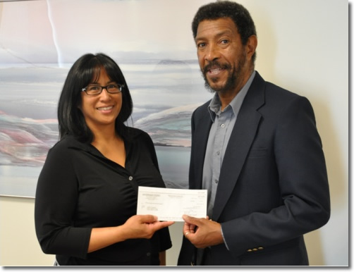 Photo of Dr. Lawford Goddard  receiving his settlement check from EEOC Attorney Linda Ordonio-Dixon